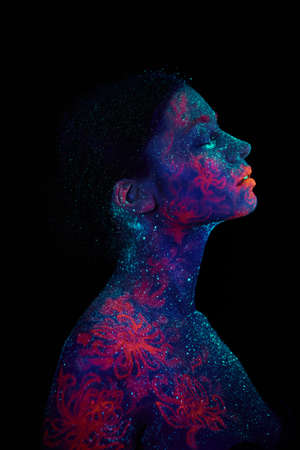 Profile portrait of a beautiful girl alien. Ultraviolet body art blue night sky jellyfish