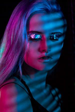 Neon lights posing in studio. Beautiful sexy girl, trendy glowing makeup, metallic silver lips Stock Photo