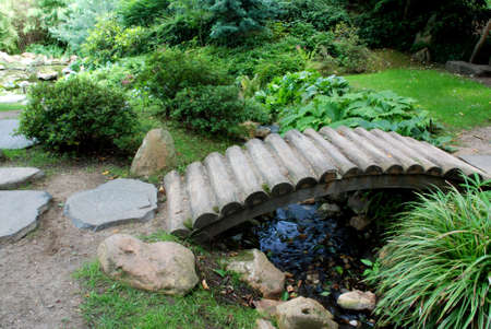 Japanese garden with many flower species and a wooden bridge Stock Photo