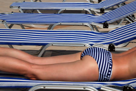 Beautiful legs of a girl in a stripped swimsuit laying on a stripped sun bed photo