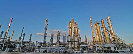 distill: Giant oil refinery with chimnies by the sunset Stock Photo