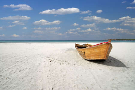 fisherman on boat: Wooden fishing boat on the white beach