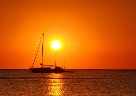 Sailing boat silhouette and golden sunset over the ocean photo