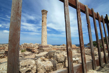 Ancient column is framed in the wooden fence photo