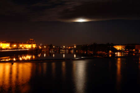 Prague in the night with a full moon mirroring in the river Moldau photo