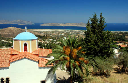 pano: Greek orthodox church, lantern and palm with a view at sea