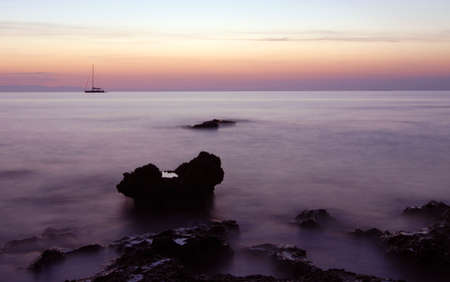 Sailing boat silhouette and rocks at  sunrise photo
