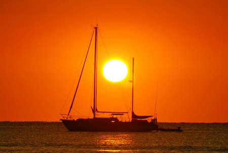 Sailing boat silhouette and golden sunrise over the ocean photo