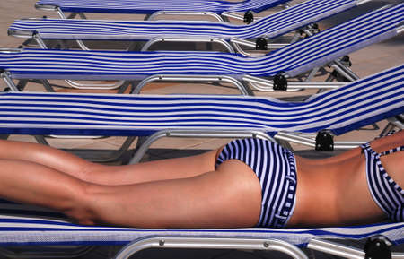 stripped: Beautiful girl in a stripped swimsuit laying on a stripped sun bed Stock Photo