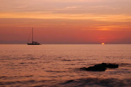 Sailing boat silhouette and sunrise - sun is just being born from the sea photo
