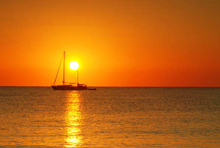 Sailing boat silhouette and golden sunrise over the ocean