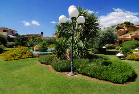 House/hotel in the beautiful summer garden with many plants and path - blue sky with clouds above and a lamp in the front Stock Photo - 2507033
