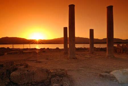 Sunset and pilars of ruins on Sardinian town of Nora photo