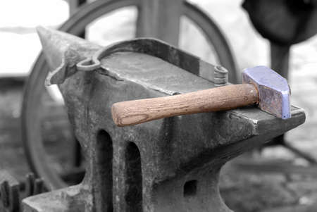 medieval blacksmith: Colorful smith hammer on a black and white anvil Stock Photo