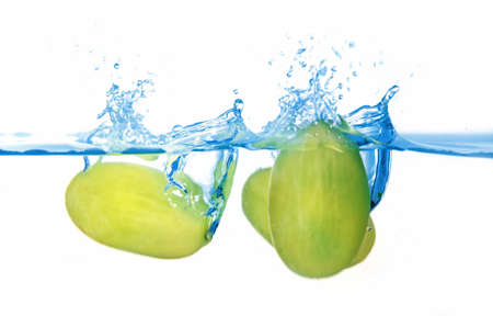 Fresh healthy green balls of grapes falling in the blue water photo