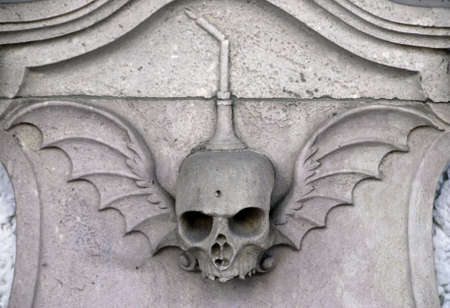 Stone winged skull carved in stone on a grave