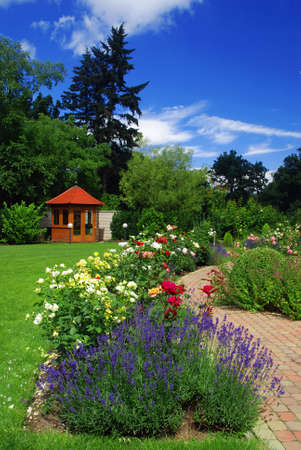 Beautiful garden with blooming roses, brick path and a small gazebo photo