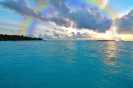 Sunset over ocean and a rainbow in the sky Stock Photo - 3773808