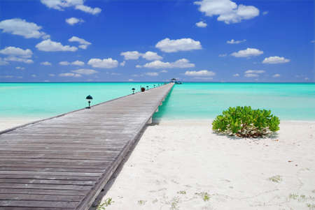 Wooden jetty on over the beautiful Maldivian beach with blue sky and clouds photo
