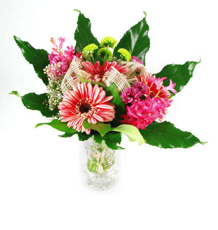 Beautiful bouquet of fresh vibrant gerbera flowers arranged in a green leaf and glass vase - isolated photo