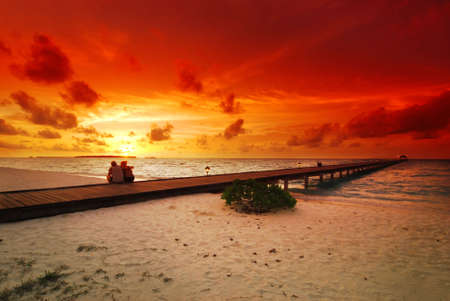 Romantic couple sitting on the jetty in the Maldives at sunset photo