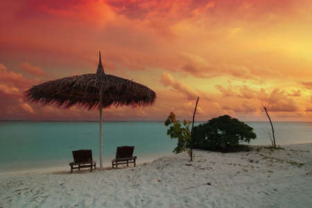 Umbrella and two chairs on the Maldivian beach at beautiful sunset photo
