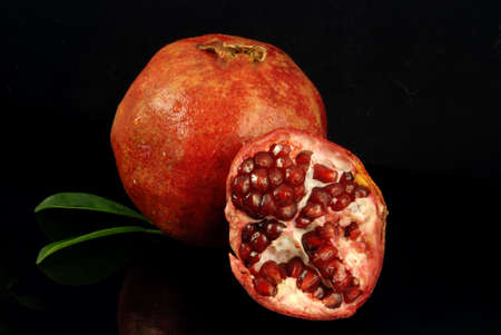 reflexive: Fresh ripe pomegranate with a half on a reflexive black