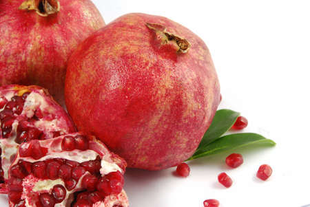Fresh ripe pomegranate with a half on white photo