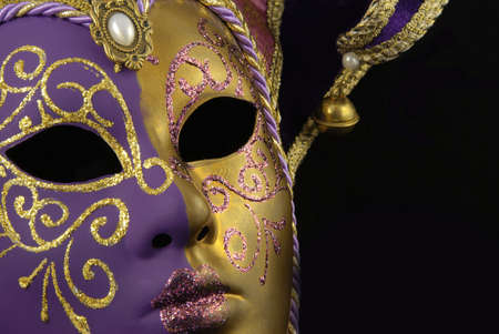 bell curve: Beautiful Venetian mask with a half from gold and a half from violet on a black background Stock Photo