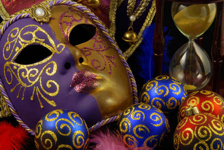 Beautiful Venetian mask on black background and christmas baubles with the similar golden motive photo