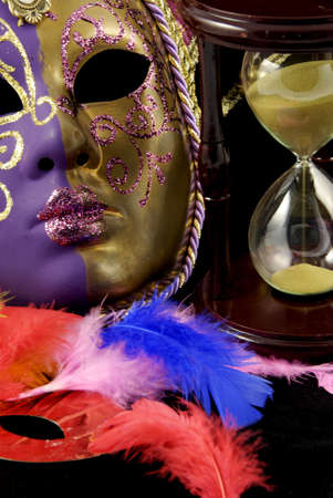 Colorful violet and gold venetian mask and hourglass photo