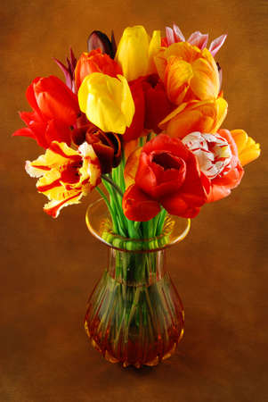 Bunch of beautiful spring flowers - colorful tulips in a vase against brown background