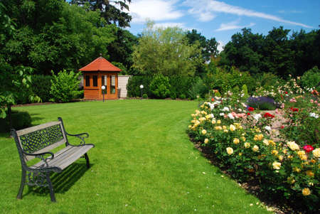 garden landscape: Beautiful garden with blooming roses, brick path, bench and a small gazebo Stock Photo