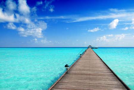 turq: Muelle de madera sobre el mar de Maldivas hermoso con el cielo azul Foto de archivo
