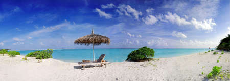Wide panoramic photo of a beautiful Maldivian beach with parasol and two deck chairs in the front