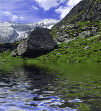 Beautiful Alpine landscape with mountains covered in snow and big boulder  on the grass reflectiong in the lake photo