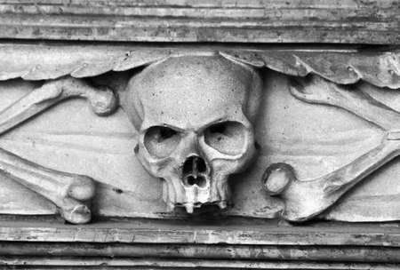 Stone skull carved in tombstone on a grave. Black and white Stock Photo - 5813900