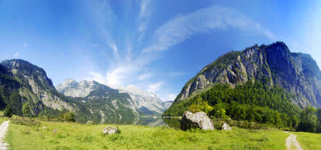 Alpine peaks with lake and green meadow in panoramic composition photo