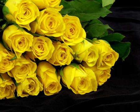 Yellow roses bunch is lying on a black silk photo