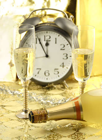 Celebration of the New Year with two glasses of champagne and bottle in the front and blurred alarm clock showing 12 PM in the back. Golden touch Stock Photo - 5814083