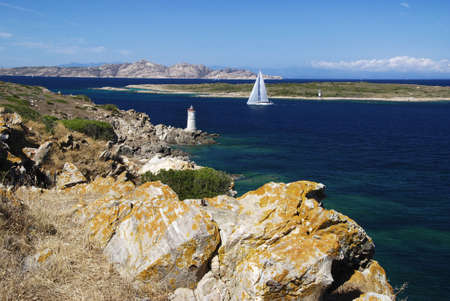 Lighthouse on Sardinian rocks and a yacht sailing in the sea photo
