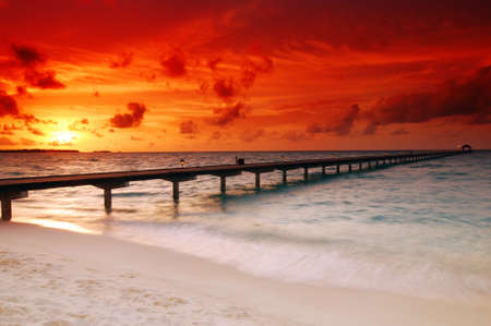 Gorgeous sunset over the sea and a jetty in the tropical paradise of Caribbean photo