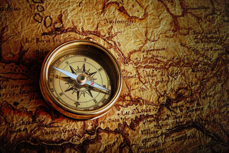 vintage compass: Old brass compass lying on a very old map