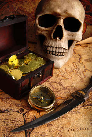 Pirate treasure. Old brass compass lying on a very old map with treasure chest full of golden coins, skull and knife photo
