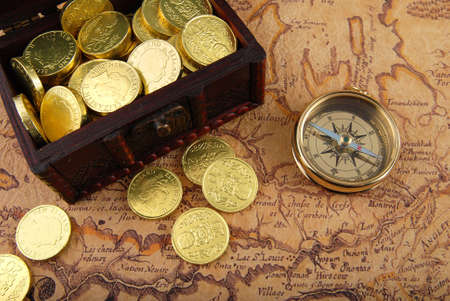 Old brass compass lying on a very old map with treasure chest full of golden coins photo
