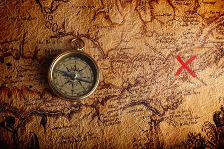 schatkaart: Oude koperen kompas, liggend op een zeer oude kaart toont de weg naar de schat  Stockfoto