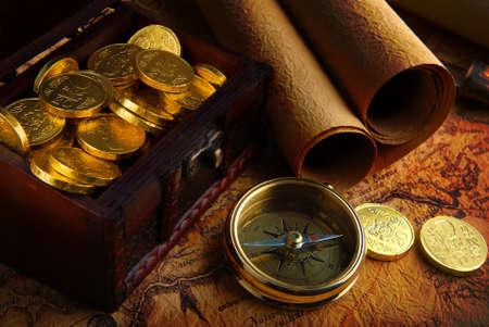 oude munten: Oude koperen kompas, liggend op een zeer oude kaart met schat kist vol gouden munten  Stockfoto
