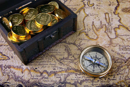treasure: Old brass compass lying on a very old map with treasure chest full of golden coins Stock Photo