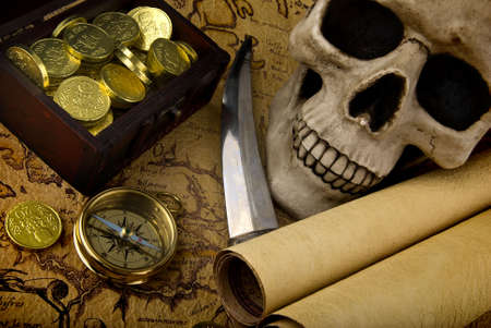 Pirate treasure. Old brass compass lying on a very old map with treasure chest full of golden coins, skull and knife Stock Photo - 6850410