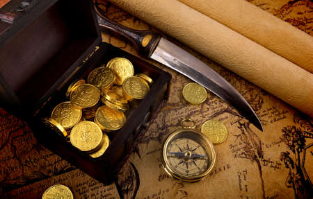 Old brass compass lying on a very old map with treasure chest full of golden coins Stock Photo - 6850411